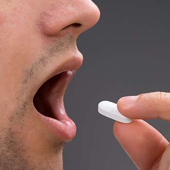 Closeup of patient taking oral sedative pill