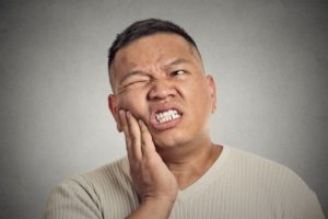 Man with tooth pain put his hand on his cheek